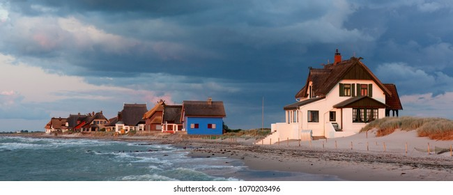 Houses at the beach near Heiligenhafen at the Baltic Sea, Schleswig-Holstein, Germany in sunset light with dramatic sky.