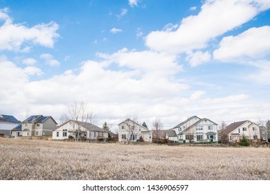 Houses behind grassland with blue sky