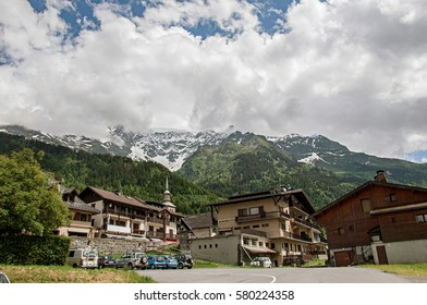 Houses and bellow tower in front of snowy mountains in a sunny day at Les-Contamines-Montjoie. A small alpine village located in the Haute-Savoie Province, near the Mont Blanc in the French Alps.