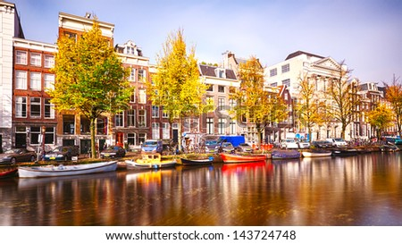 Houses, boats and a canal in Amsterdam, photographed in the autumn. This is a long exposure, some motion blur of the boats is present.