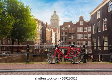 Houses and Boats on Amsterdam Canal. Morning photo of colored houses in the Dutch style and bridge with a red bicycle in the foreground