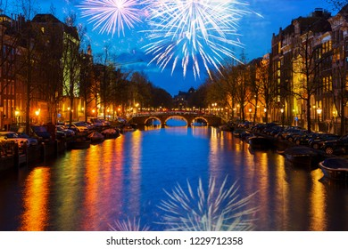 Houses and bridges over canal with lights and reflections at night with fireworks, Amsterdam, Netherlands