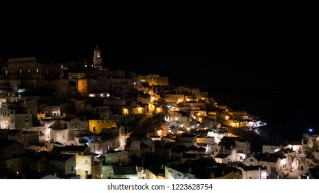 Houses built into the rock in the cave city of Matera (Sassi di Matera), Basilicata Italy. Photo taken at night. Matera has been designated European Capital of Culture for 2019.