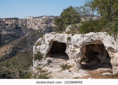 Houses built into the rock in the cave city of Matera (Sassi di Matera), Basilicata Italy. Matera has been designated European Capital of Culture for 2019. Caves across the ravine in the foreground.