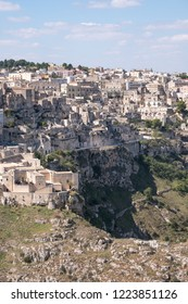 Houses built into the rock in the cave city of Matera (Sassi di Matera), Basilicata Italy. Matera has been designated European Capital of Culture for 2019. Ravine in foreground.