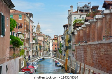 Houses by the canal and boats on the canal. At Venice city, Italy. In May 2018.