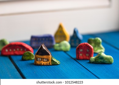 houses and cars handmade salt dough on dark blue and white background. Copy space, toning. Concept childhood and creativity, soft focus