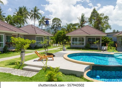 Houses, deck chair and beautiful swimming pool with palm tree, Samui, Thailand, Scenic landscape