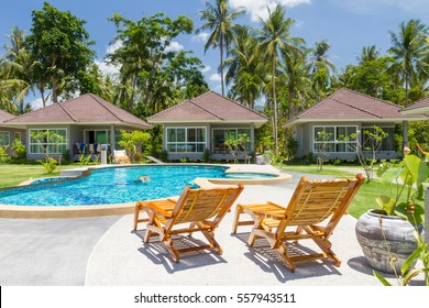 Houses, deck chair and beautiful swimming pool with palm tree and sky background, Samui, Thailand, Scenic landscape