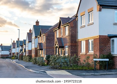 Houses in England with typical red bricks at sunset - Main street in a new estate with typical British houses on the side - Real estate and buildings concepts in UK
