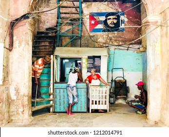 House's entrance with little shop and Cuban flag with Che Guevara portrait painted on a shabby old wall. Old Havana. Cuba. 10/04/2018