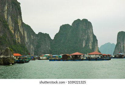 Houses floating on pontoon in Halong Bay, Vietnam. Many display the Vietnamese flag. Behind are tall limestone peaks covered with trees. The sky is overcast.