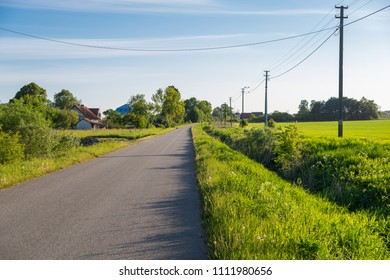 Houses in the green by country road with blue clean sky