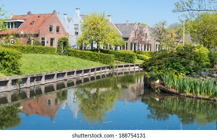 Houses in the historic Dutch village of Drimmelen reflected in the mirror smooth water surface of the canal.