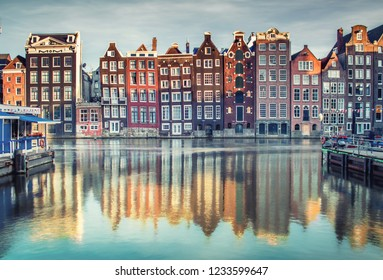 Houses lining Damrak canal in Amsterdam, Netherlands at sunset