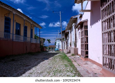 Houses and old car on typical street in Trinidad, Cuba on sunny day.
