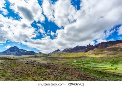 Houses on a background of mountains under cloudy sky in Iceland
