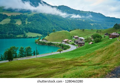 Houses on the bank of Lungern Lake - Lungernsee, canton of Obwalden, Switzerland. Landscape photo was taken in a rainy day in June.