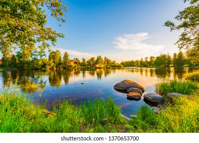 Houses on the banks of the river. Ducks swim in the pond. Sunset. Blue sky. Beautiful nature. Summer evening. View from the grassy shore.