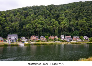 Houses on riverbank of river Meuse in Godinne, Ardennes region, Belgium. River Meuse between Dinant and Namur, Ardennes, Wallonia, Belgium.