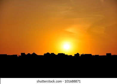 Houses outline against a sunset background