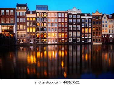 Houses over canal with reflections illuminated at night, Amsterdam, Netherlands, toned