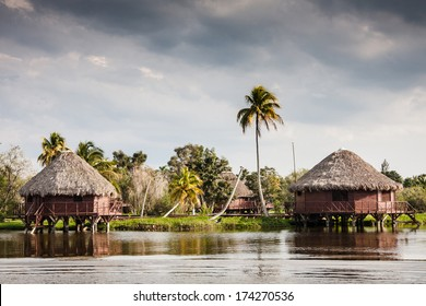 Houses over pillars at a Black lake in the cuban tourist village of Guama, Cuba