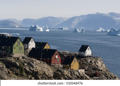 Houses overlook an iceberg-laden fjord of Baffin Bay in the small village of Uummannaq, Greenland.