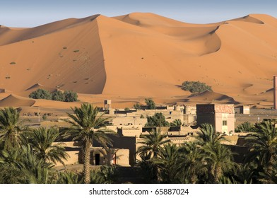 Houses and palm trees on the border with large sand dunes of the Sahara desert - Best of Morocco.