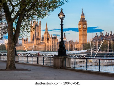 The Houses of Parliament and the Big Ben in London seen from the Queen's Walk riverfront at dawn