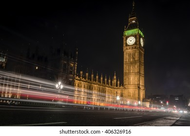 The Houses of Parliament and Elizabeth tower housing the Big Ben at night with light trails caused by cars and buses in London at night.
