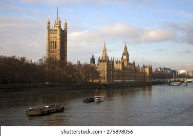 The Houses of Parliament in London, England, standing alongside the River Thames as barges sail past.