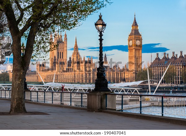The Houses of Parliament in Westminster and the Big Ben tower in London seen from the Queen's Walk riverfront at dawn