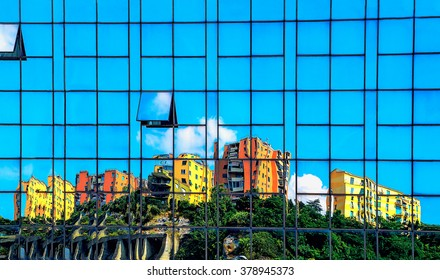 houses reflected in the wall of a skyscraper