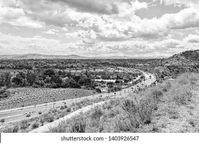 Houses and roads heading east in inland Southern California on spring afternoon in black and white