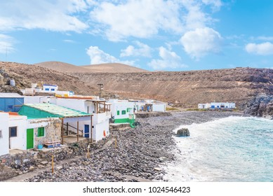 houses of small fishermen's village against cliffs and ocean at Fuerteventura island