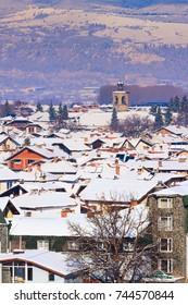 Houses with snow roofs and church tower panorama of bulgarian ski resort Bansko, Bulgaria