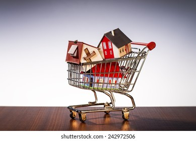 Houses are stacked in a shopping cart.