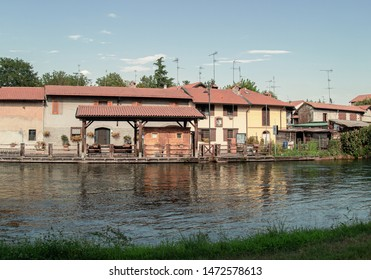 houses and vegetable gardens on the canal in the countryside outside Milan
