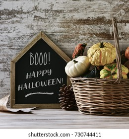 a house-shaped chalkboard with the text booo happy halloween, and a worn wicker basket with an assortment of different pumpkins on a rustic wooden table