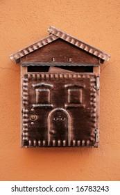 House-shaped metal mailbox against orange wall.