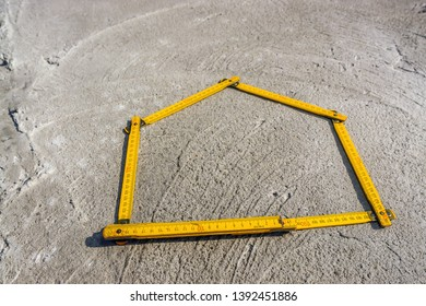 House-shaped yellow wooden folding ruler placed on concrete foundation surface