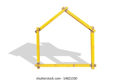 House-shaped yellow wooden folding ruler casting house shadow over white background