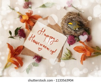 "housewarming concept, wooden bird in the nest,letter with inscription ""happy housewarming!"" lilies on the white background"