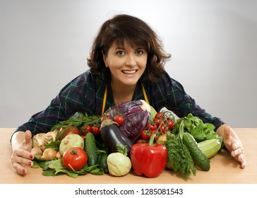 Housewife in apron with a bunch of vegetables on the table