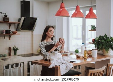Housewife in apron is cooking bakery in kitchen. She is standing at table and holding jar while looking at it and trying to find out what is inside
