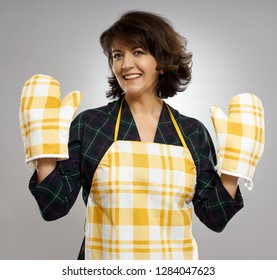 Housewife with apron and cooking gloves over gray background