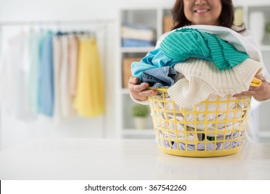 Housewife with big basket of freshly washed clothes