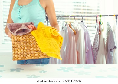 Housewife bringing a huge pile of laundry on the ironing board