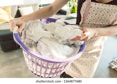 Housewife carrying the dirty laundry in a basket to the washing, close-up